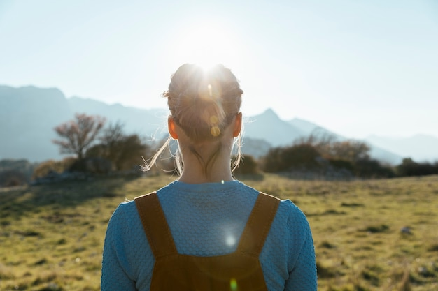 Женщина сталкивается с солнцем в природе