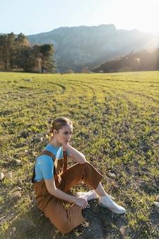 Длинный выстрел женщина сидит на траве