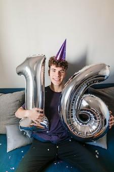 Счастливый подросток держит воздушные шары на день рождения
