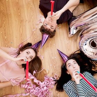 Вид сверху друзей, лежащих на полу