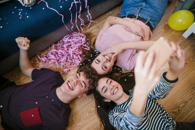Счастливые подростки, делающие селфи лежа на полу