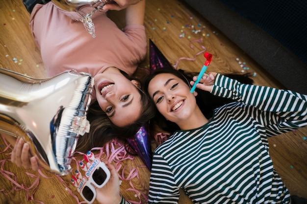Вид сверху счастливых девушек, лежащих на полу