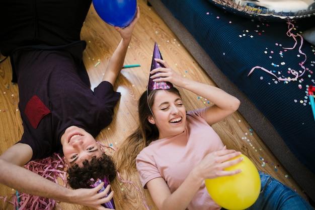 Высокий угол улыбающихся друзей, лежащих на полу