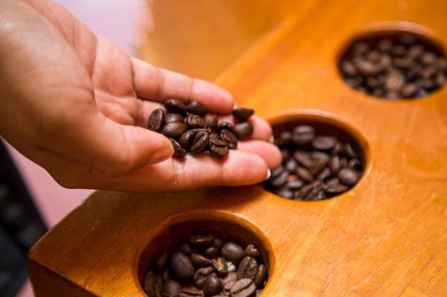 コーヒー豆を持っている女性の手のクローズアップ
