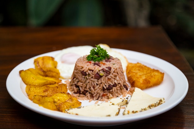 Костариканская традиционная еда в белой тарелке на деревянный стол
