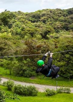 コスタリカの森でジップラインアドベンチャーのライドを楽しむ人