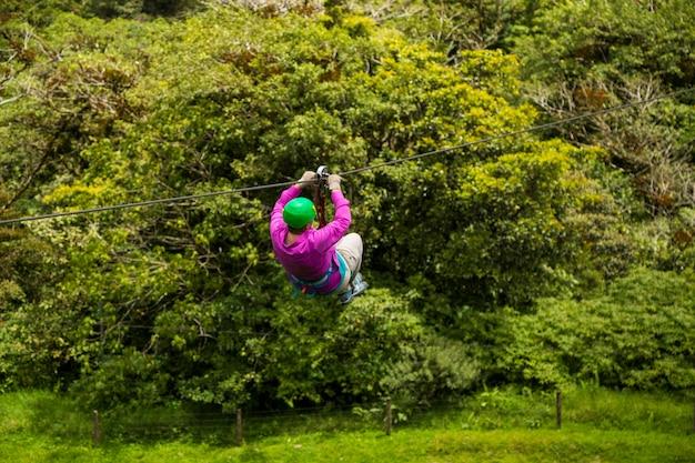 コスタリカの熱帯雨林でジップラインに乗る人