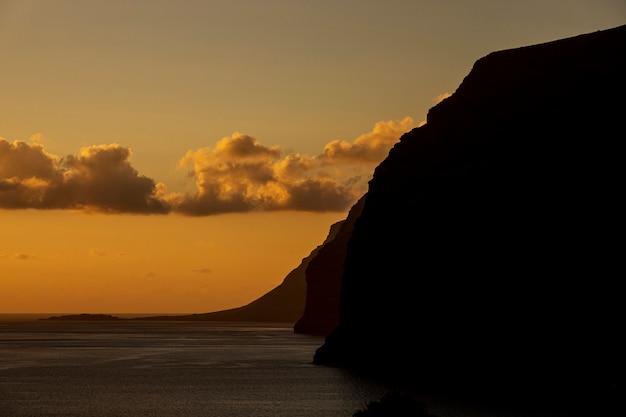 夕日の海辺の高い崖