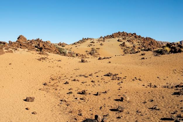 澄んだ青い空と岩が多い砂漠