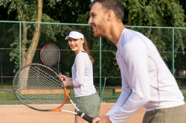 デュオでテニスをするカップル