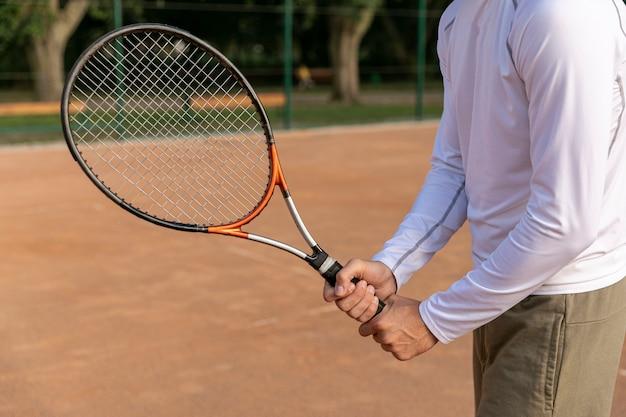 テニスラケットを保持しているクローズアップ男