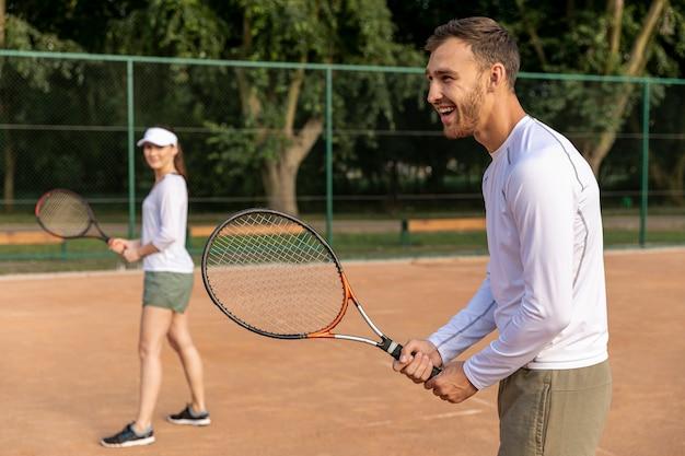 Пара играет в теннис в дуэте