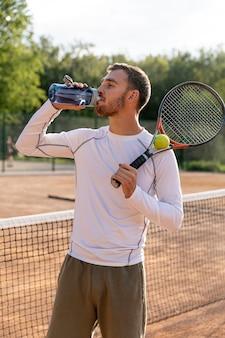 Человек вид спереди увлажняющий на теннисном корте