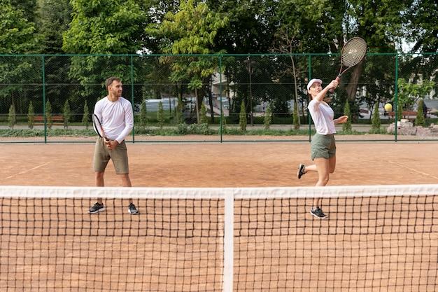 Пара вид спереди, играя в теннис