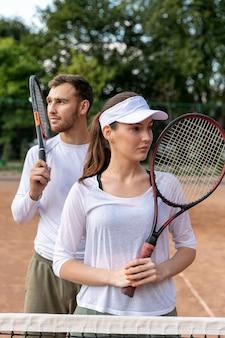 テニスコートで正面の幸せなカップル