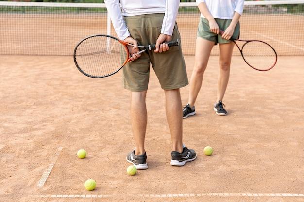 テニスコートで休憩するカップル