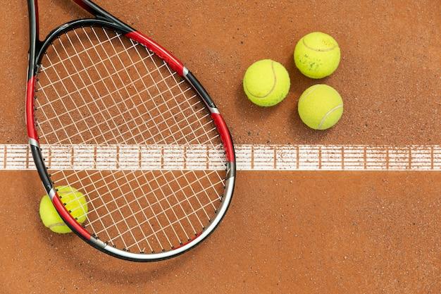 Вид сверху ракетки и теннисных мячей на площадке