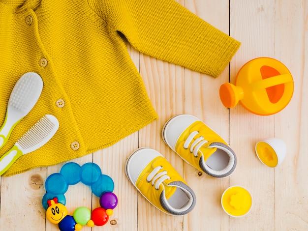 Вид сверху желтый свитер с игрушками