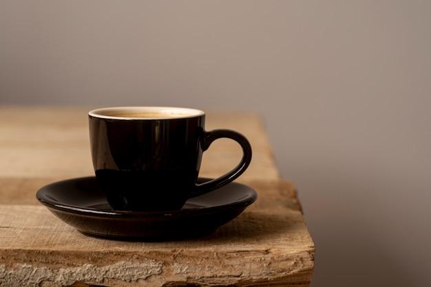 Вид спереди чашка кофе на деревянный стол