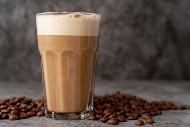 コーヒー豆とカプチーノのクローズアップガラス