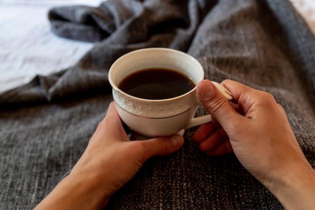 一杯のコーヒーを保持しているベッドでクローズアップ人