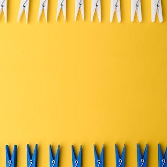 黄色の背景とトップビュー洗濯はさみ