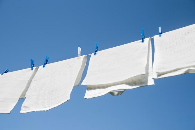 Белое белье висит на веревочке на улице