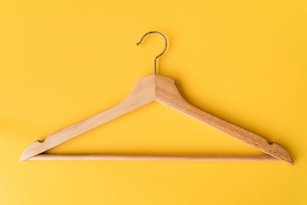 黄色の背景のトップビュー木製ハンガー