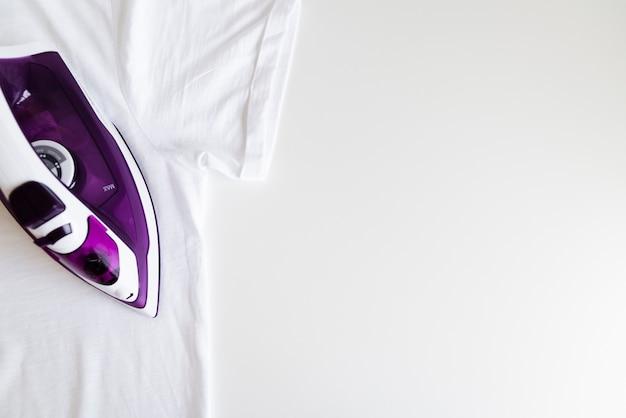 Вид сверху фиолетовый утюг с белым фоном