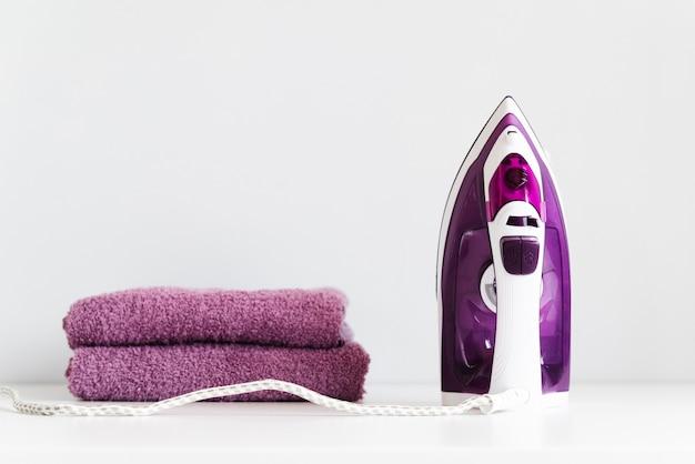 Вид спереди фиолетового утюга со сложенными полотенцами