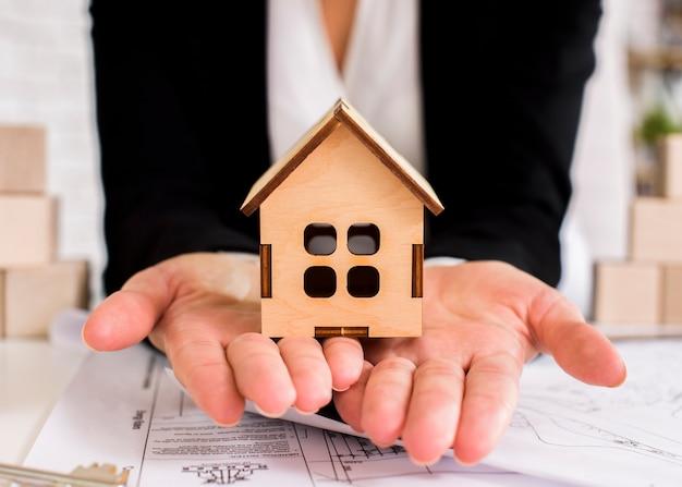 Деревянный дом крупным планом на руках женщины