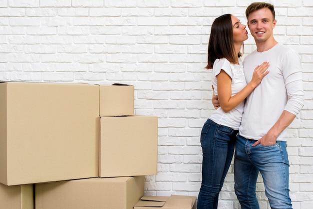 Девушка целует своего парня во время улыбки
