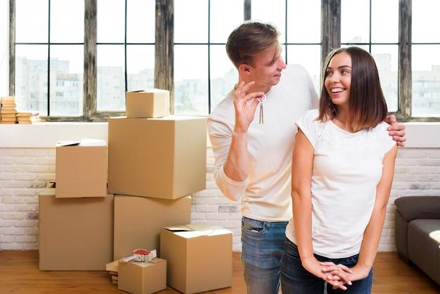 Молодой человек показывает ключи от своей счастливой женщины