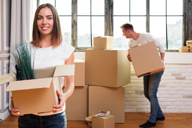 Женщина держит картонную коробку с растениями
