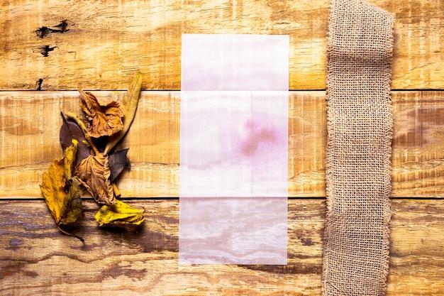 木製の背景と黄麻布の横にある薄っぺらな紙
