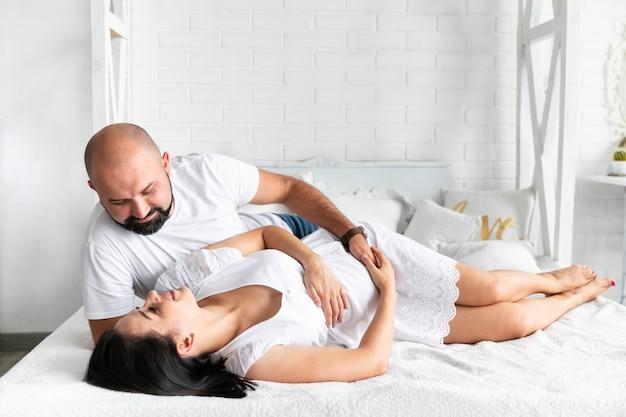 ロングショットの両親がベッドに寄り添う