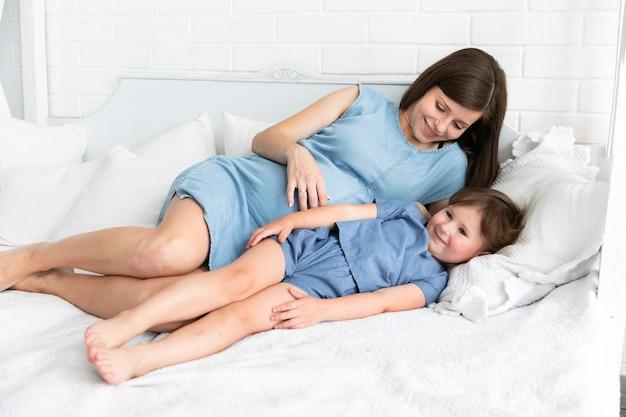 幸せな母と娘がベッドに滞在