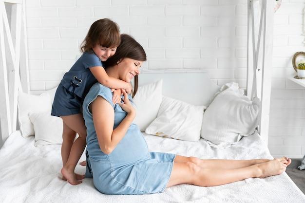 Маленькая дочь обнимает маму сзади