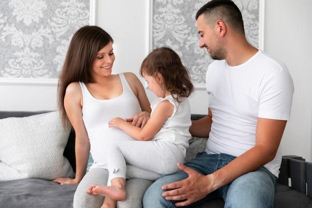 ミディアムショットの両親と娘が新しいメンバーを待っています