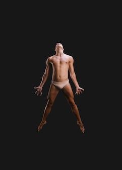 上半身裸のダンサーがパフォーマンス中にジャンプ
