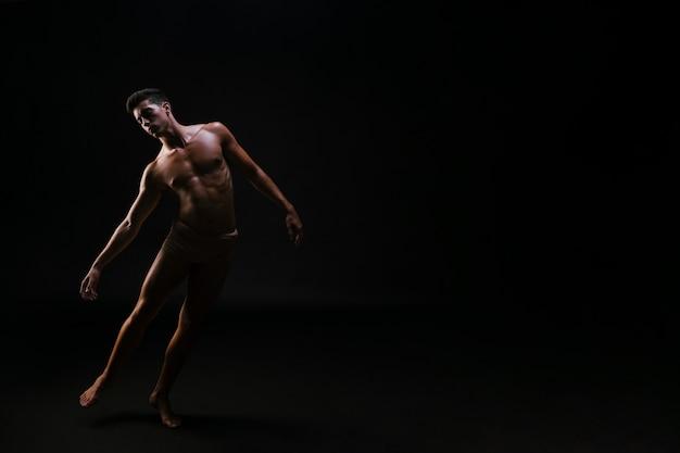 黒の背景に立っている裸の運動曲がった男