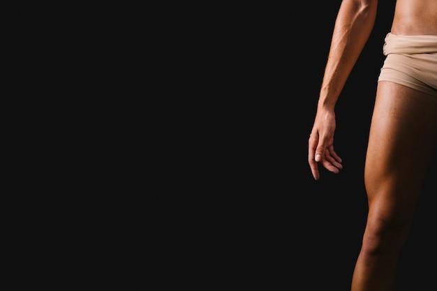 黒の背景に立っている運動の裸の男性