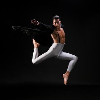 Молодой спортивный мужчина в стильной одежде прыгает и танцует