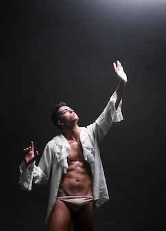 光に手を伸ばして筋肉の男性