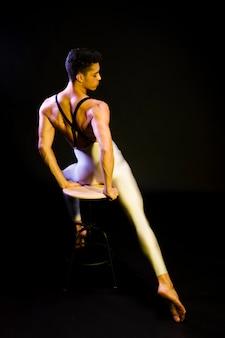 スポットライトで座っている官能的な男性バレエダンサー