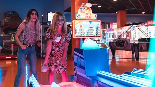 幸せな女性がアーケードゲームをプレイ