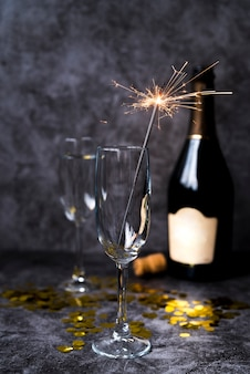 セメントコンクリート背景にクリスマス線香花火と空の透明なワイングラス