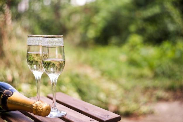 Крупный план бокалов для шампанского на деревянном столе на открытом воздухе