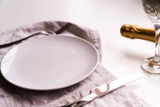 白い背景の上のシャンパンのボトルの近くのナプキンにバターナイフで空のプレート
