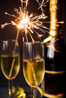 Горящий бенгальский огонь в бокал с шампанским на темном фоне